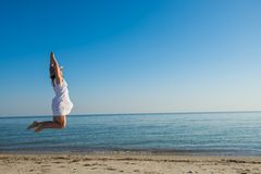 Joyful woman, delighted, jumps on the beach Royalty Free Stock Photo