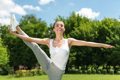 Joyful woman doing sport exercises. Share positivity. Cheerful smiling delighted attractive woman holding her leg up and expressing gladness while doing sport stock images
