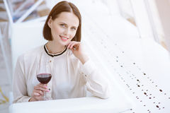 Joyful woman drinking alcohol beverage in restaurant. Rich young businesswoman enjoying red wine in cafe. She is looking at camera and flirting. Lady is sitting Stock Image