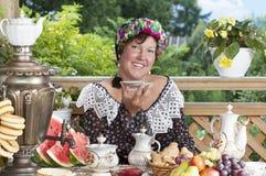 Joyful woman drinking tea outdoors Stock Image