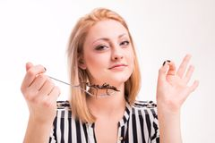 Joyful woman eating insects with a fork in a restaurant Royalty Free Stock Photo