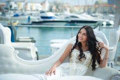 Joyful woman in elegant dress on sunny day at marina Stock Image