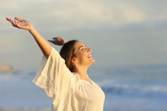 Joyful woman enjoying a day on the beach. Raising arms at sunset stock photo