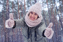 Joyful woman enjoying the winter snow looking at the camera unde Stock Images