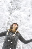 Joyful woman enjoying the winter snow. Looking up into the falling snowflakes with a happy smile and her arms extended, against a background of snowy vegetation Stock Photos