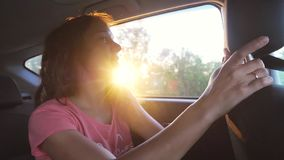 Joyful woman enjoys traveling by car in summertime. Sunset rays. Slow motion. Happy woman enjoys traveling by car in summertime. Hand in the air through the stock footage