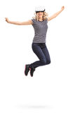 Joyful woman experiencing virtual reality. Vertical shot of a young joyful woman experiencing virtual reality and jumping shot in mid-air isolated on white Royalty Free Stock Image
