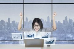 Joyful woman with financial chart on laptop Royalty Free Stock Photography