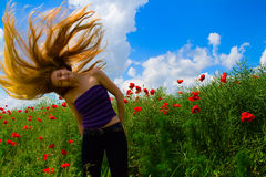 Joyful woman with flying hair in poppy field Royalty Free Stock Images