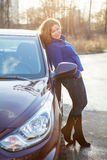 Joyful woman in full length leaned against car Stock Image