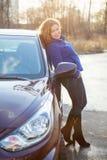 Joyful woman in full length leaned against car Stock Image