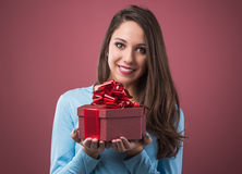 Joyful woman with gift box. Joyful beautiful young woman holding a gift box with red ribbon Stock Images