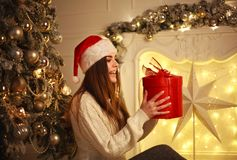 Joyful woman with gift in Santa hat on background of Christmas Stock Photos