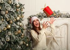Joyful woman with gift in Santa hat on background of Christmas Stock Photo