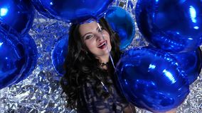 Joyful woman in good mood among inflatable balloons at evening event. Joyful woman in good mood among inflatable balloons on background of shiny wall at evening stock footage