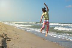 Joyful woman having fun on the beach. Jumping and enjoying life. Wonderful sunny day on the seashore. Back view Royalty Free Stock Photo