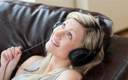 Joyful woman with headphones on lying on a sofa Royalty Free Stock Image