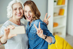 Joyful woman and her daughter making selfies Royalty Free Stock Photo