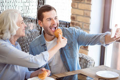 Joyful woman and his adult grandson having lunch. Pleasant time together. Joyful women and his grandson making selfies and eating croissants while resting in the Stock Image