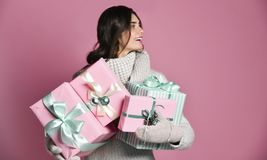 Joyful woman holding a lot of boxes with gifts on a pink background. royalty free stock photography