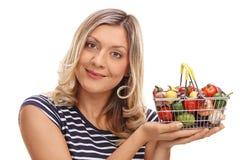 Joyful woman holding a shopping basket. Joyful woman holding a small shopping basket full of vegetables and fruits isolated on white background Stock Photography