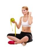 Joyful woman holds grapefruit and measurement tape Stock Photo