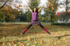 Joyful woman jumping in autumn park Stock Photo