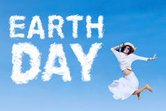 Joyful woman jumps with Earth Day text Stock Image
