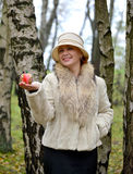 The joyful woman keeps decorative apple on a palm in a hat Stock Photos
