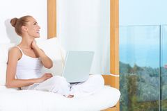 Joyful woman laughing with laptop. Joyful woman seated on white cushions laughing with with her laptop balanced on her crossed legs Stock Photos