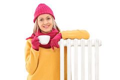 Joyful woman leaning on a radiator and holding a cup Royalty Free Stock Image