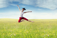 Joyful woman leaps at field in springtime Stock Image