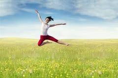 Joyful woman leaps at field in springtime Stock Image