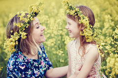 Joyful woman little girl in flower garland at yellow field Stock Photos