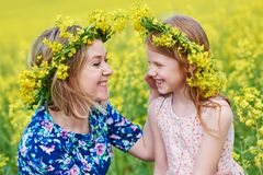 Joyful woman little girl in flower garland at yellow field. Young smiling women together with little girl in flower garland at yellow green seed meadow Royalty Free Stock Photo