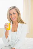Joyful woman looking at camera enjoying a glass of orange juice Stock Photography