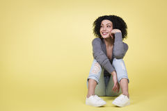 Joyful woman looking up sitting on isolated yellow  background. Royalty Free Stock Images