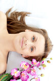Joyful woman lying on a massage table with flower Stock Images