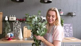 Joyful woman makes a bouquet for table setting. The blonde is making a bouquet of eucalyptus. Festive table setting