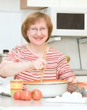 Joyful woman making dough in the kitchen at home Royalty Free Stock Photography