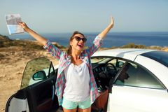 Joyful woman with a map in her hand traveling on a cabriolet Stock Photo