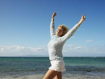 Joyful woman in Maui. Portrait of attractive young blond woman smiling with arms raised in air on Maui, Hawaii beach stock image