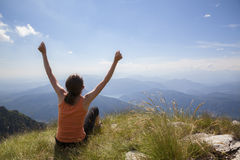 Joyful woman on mountain top. Happy woman with raised arms sitting on mountain top looking at mountain landscape and blue sky on Monte Generoso Stock Photo