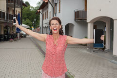 Joyful Woman with Open Arms on City Street Royalty Free Stock Photos