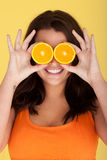Joyful Woman With Orange Slices Over Eyes Stock Photography