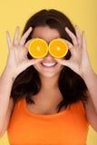 Joyful Woman With Orange Slices Over Eyes Stock Photography