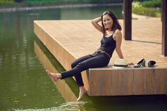 Joyful Woman on Pier. Full length portrait of joyful young woman looking at camera with charming smile while sitting on wooden pier and splashing water with her Stock Images