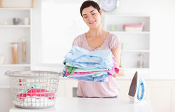Joyful Woman with a pile of clothes Stock Photos