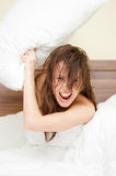 Joyful woman with pillow. In her bed Stock Images