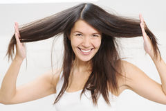 Joyful woman playing with her hair Stock Photo